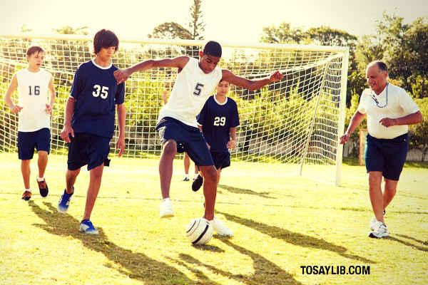 coach teaching youth playing football