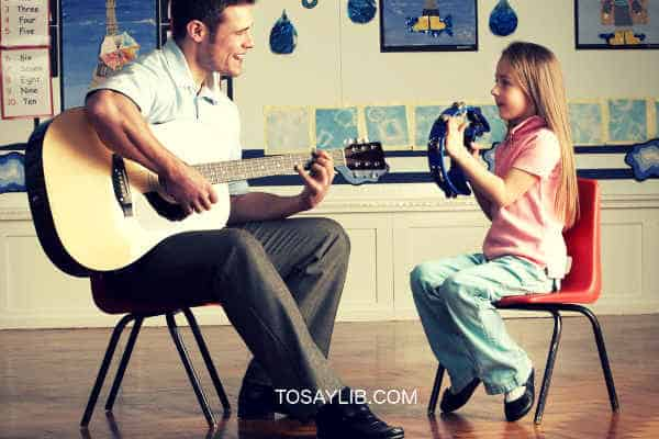 teacher teaching guitar to a girl