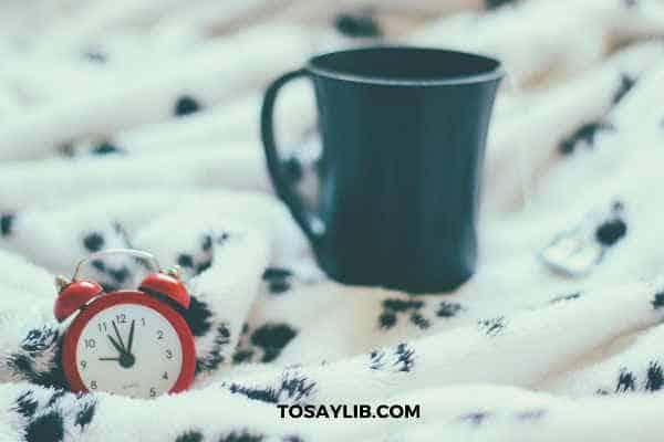 alarm clock on blanket coffee mug