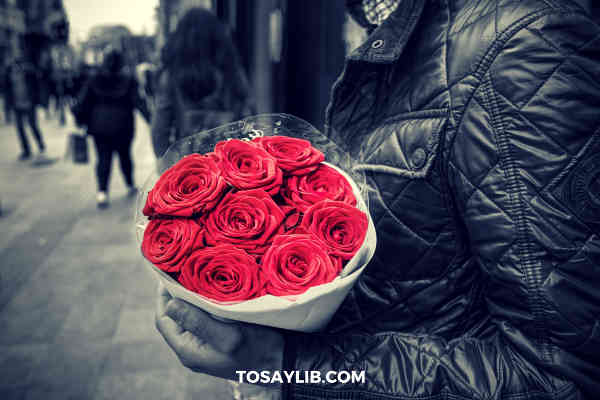 man holding a bunch of roses black and white