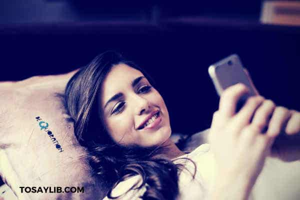 pretty girl texting in bed smiling