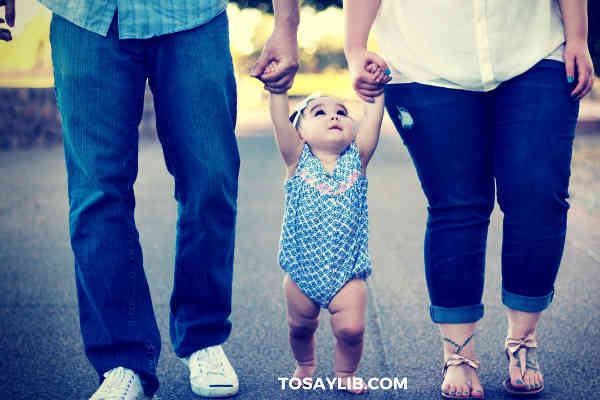 parents holding hands of a baby girl on each side walking