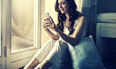 pretty girl looking at phone in bedroom
