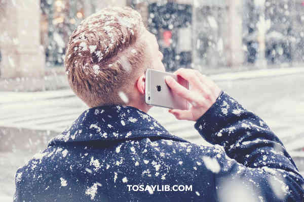 man talking on iphone snowing