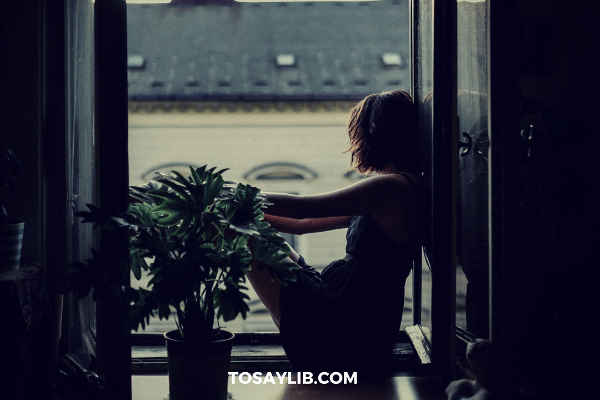 girl being sad sitting next to window