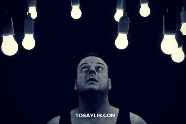 performer looking at light bulbs