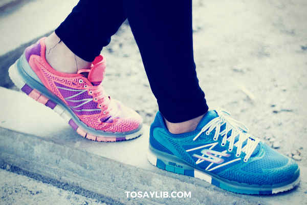 girl wearing sneakers in different colors