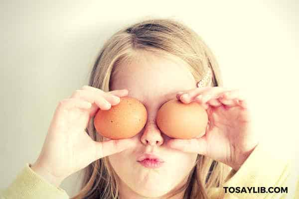 little girl holding eggs on her eyes