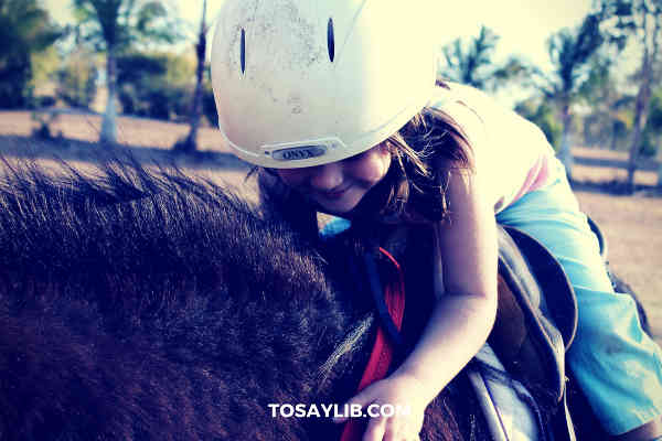 little girl riding on a pony