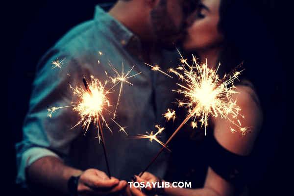couples kissing holding firework sticks