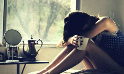 sad-girl-sitting-in-bed-holding-mug