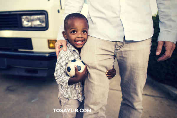 little boy holding a football and leg of his dad