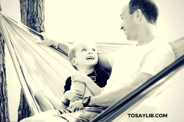 dad sitting on hammock with son