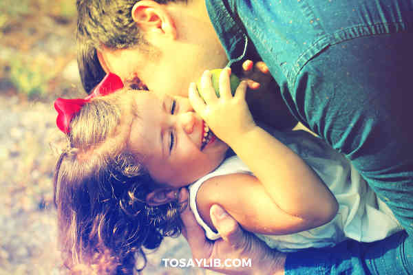 dad kissing hugging playing with daughter