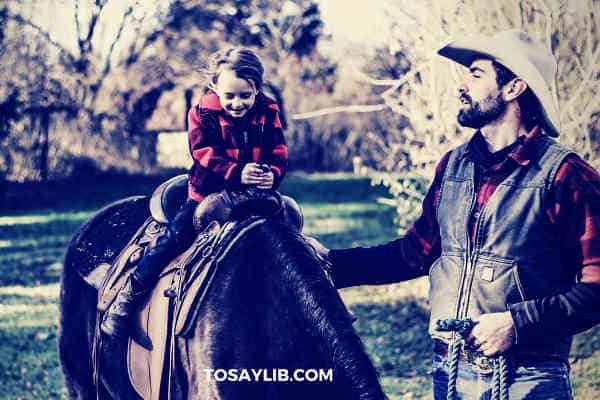 dad teaching daughter how to ride on pony