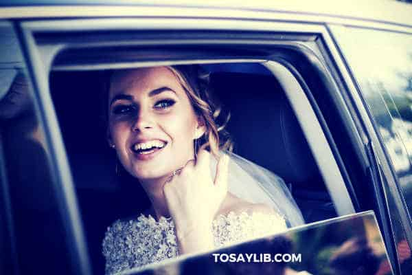 bride sitting in the car smiling watching invitees