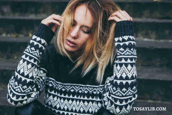 in sweater looking upset