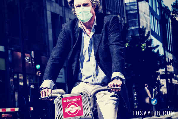 man wearing mask riding bicycle