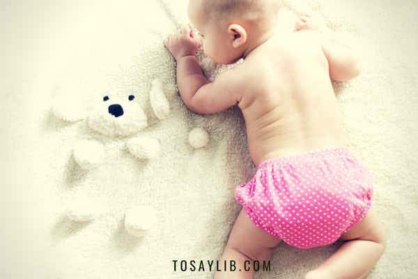 baby weraing diaper crawling on bed