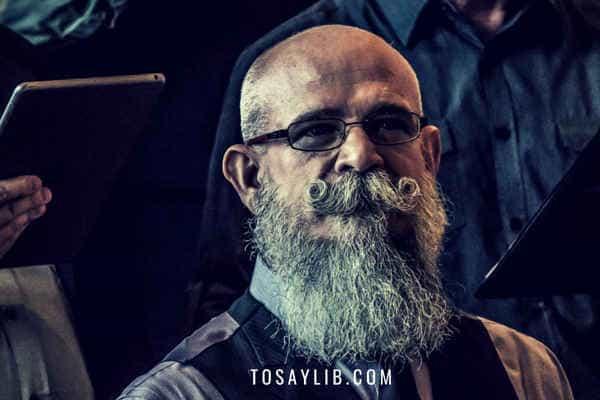 man in sixties wear beard listening cafefully
