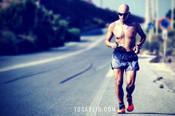 man running short earphone on the road sunglasses