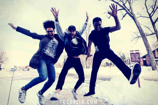 men happy jumping on snow