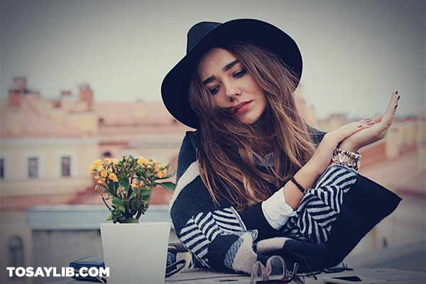 01 fashionable woman with a hat sitting outdoors
