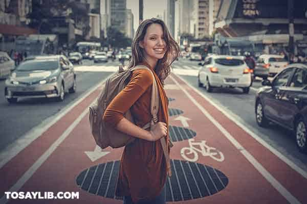 16 Happy girl with backpack in the middle of a street looking back
