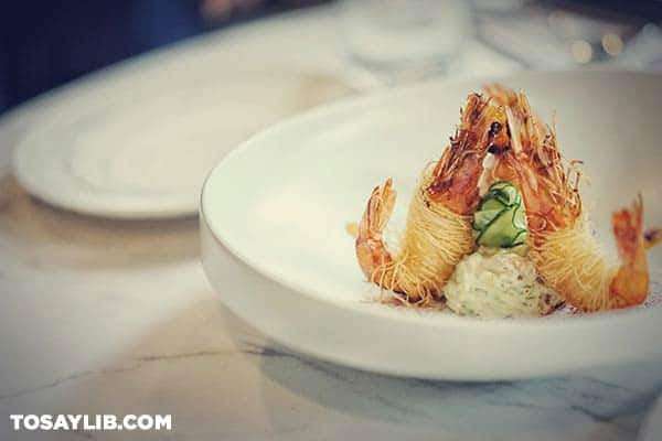 01 Three cooked shrimp arranged on a white plate