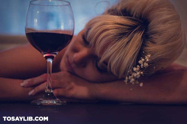 22 Woman resting her head on table beside half finished wine