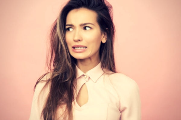 Feature-Woman-standing-against-a-pink-wall-looking-uncertain
