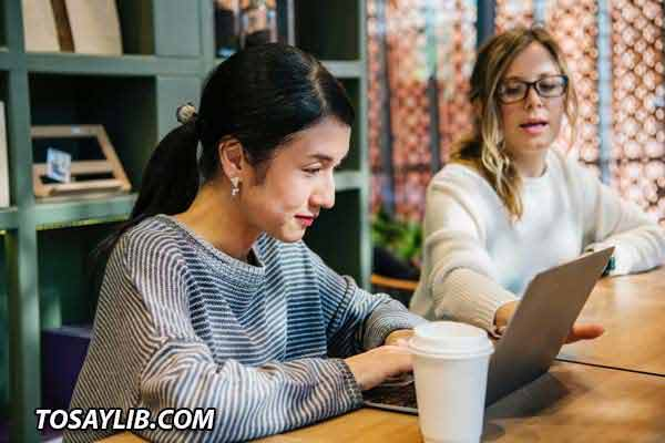 Photo of a newcome listening to her colleague showing something on her laptop while having coffee.