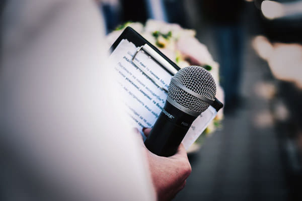 08-Featured-Photo-of-a-person-holding-a-microphone-while-holding-a-clipboard-and-a-boquet-of-flowers