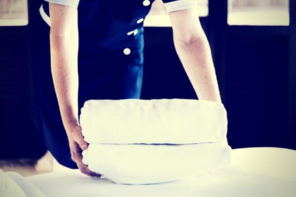 14-feature-Hotel-staff-folding-white-towels-white-bedsheet-dark-blue-uniform