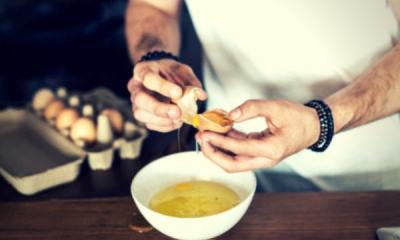 16-feature-man-white-shirt-break-eggs-eggwhite-wooden-table