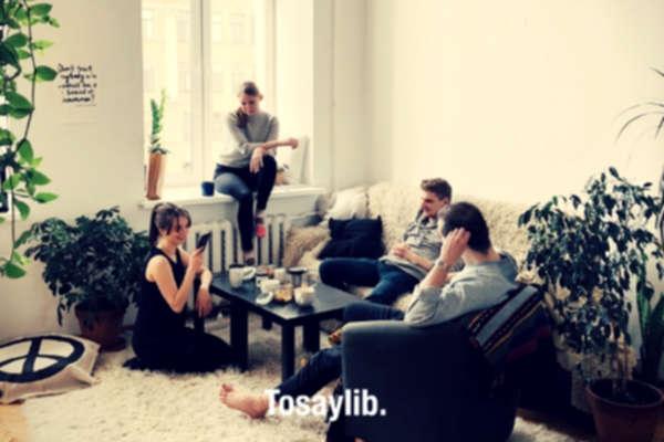 people gathered inside house sitting on sofa white carpet