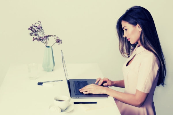 05-feature-woman-in-pink-dress-using-laptop-computer-coffee-vase-white