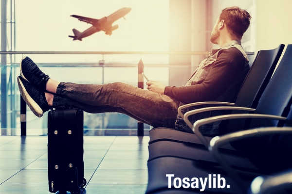 man casual clothes sitting luggage bag airplane sky