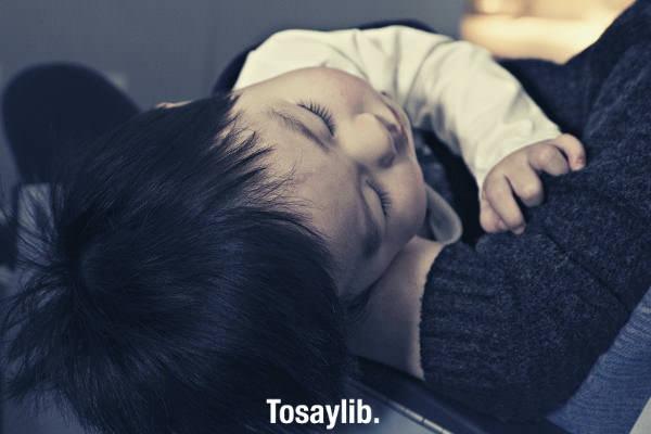 toddler boy sleeping sick lying on mom s arms