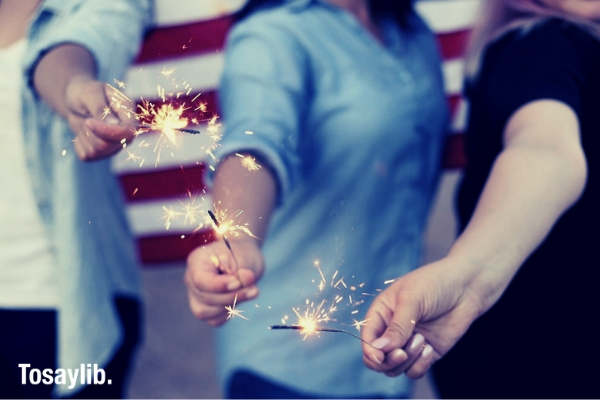 women holding sparklers burning fireworks fire american flag background