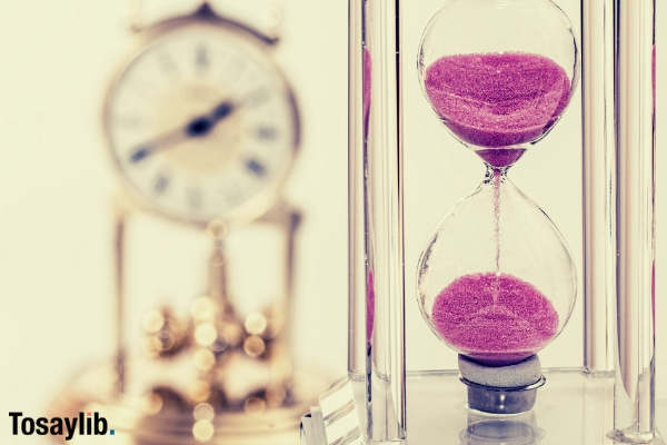 hourglass pink sand dripping clock blur background