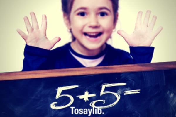 little girl counting blue jacket green blackboard five plus five written