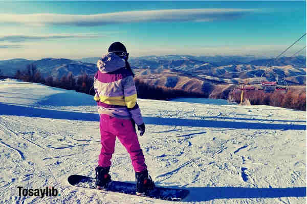 person snowboarding on field pink snow suit snow sky mountains