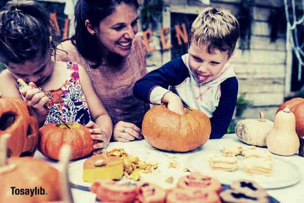 woman cuddling two kids carving pumpkins on table