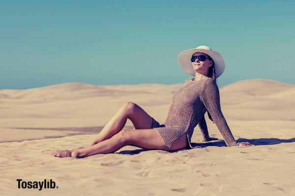 portrait of woman sitting on sand at beach against sky wearing brown dress hat shades