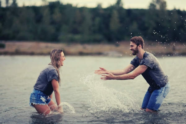 33-feature-man-and-woman-playing-on-body-of-water-trees
