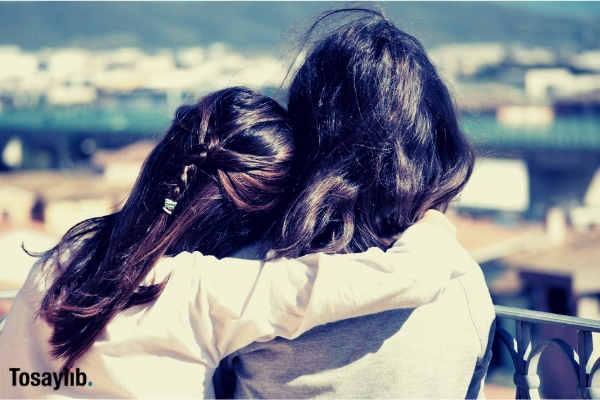 girl hugging friend facing bakward blur