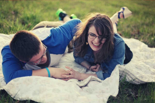 feature-happy-couple-with-eyeglasses-lying-on-green-grass