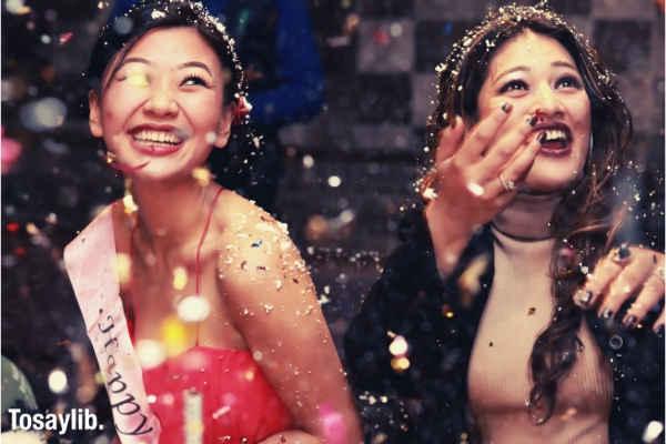 two women having fun birthday party guy at back confetti cake