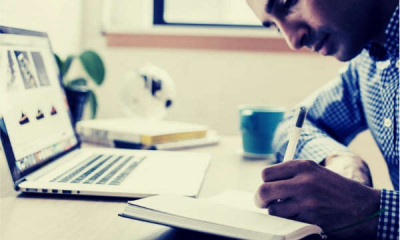 08-man-using-ballpoint-pen-writing-notebook-laptop-bokeh-shot